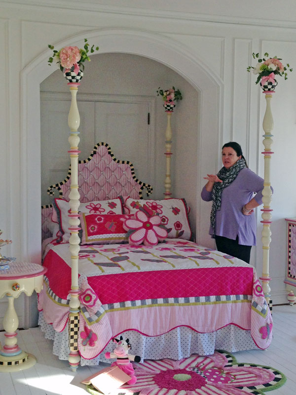 Kim contemplating the finishing touches on the dreamiest bed, complete with fresh bouquets in the vases.